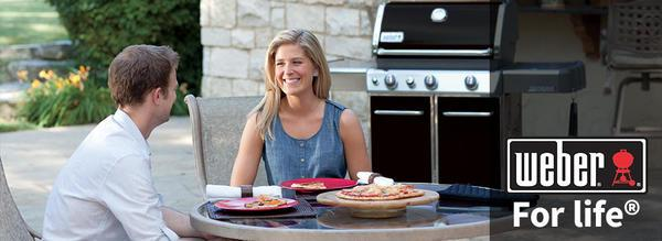 A couple eating food outside with a Weber grill in the background